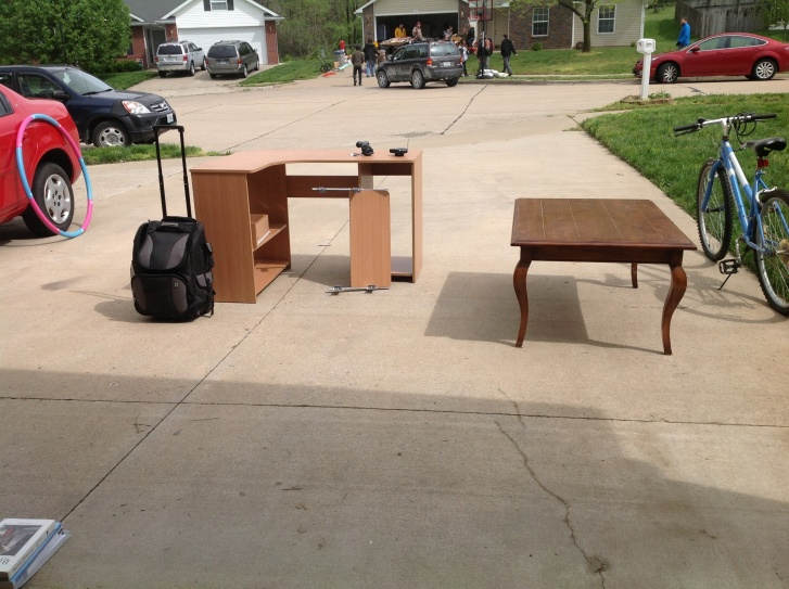 Selling all my belongings at a community garage sale to raise travel money.